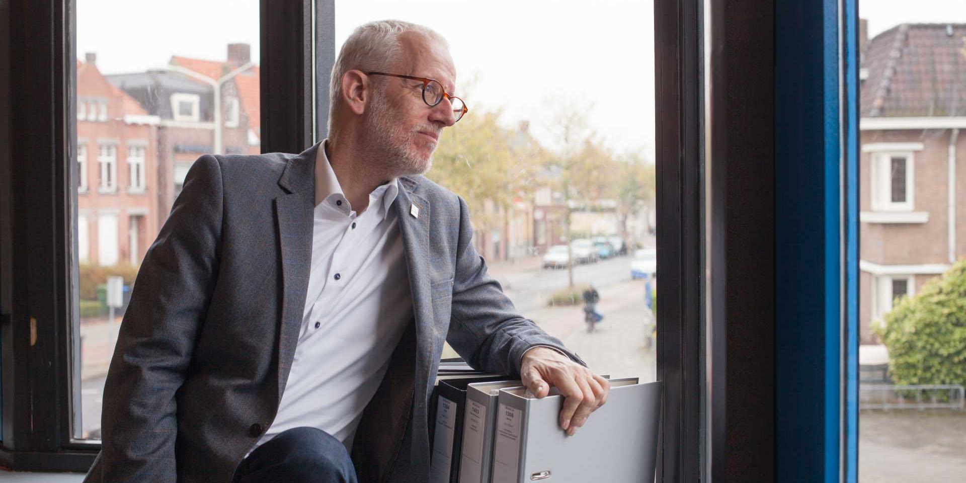 Tim de Jonge voor het raam van zijn kantoor.